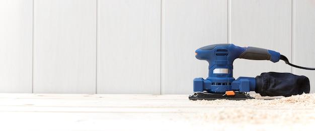 Detalle de una lijadora eléctrica en el suelo de madera natural de su casa.