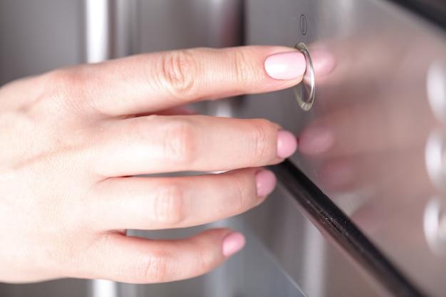 Detalle de la mano femenina mientras usa el microondas