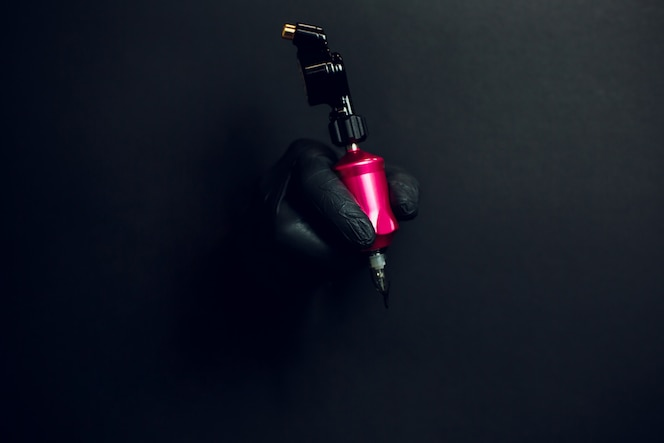 Detalle de mano con maquina rotativa de tatuaje