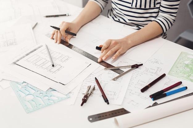 Detalle de manos de joven ingeniera profesional femenina haciendo ediciones con regla y trazador de líneas en el nuevo proyecto de equipo. trabajo en equipo y negocios.