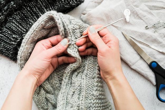 Detalle de las manos de una mujer de ganchillo con aguja de crochet.