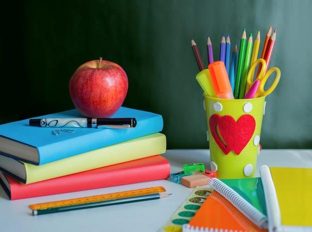 Detalle de la mesa de profesores con útiles escolares coloridos y manzana roja y pizarra verde detrás