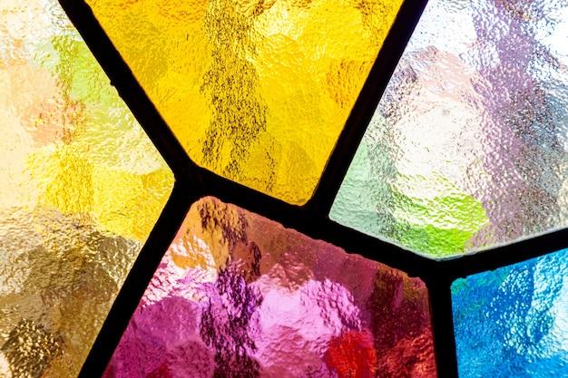 Detalle de un mosaico multicolor de colores translúcidos en las vidrieras de una ventana de la iglesia.