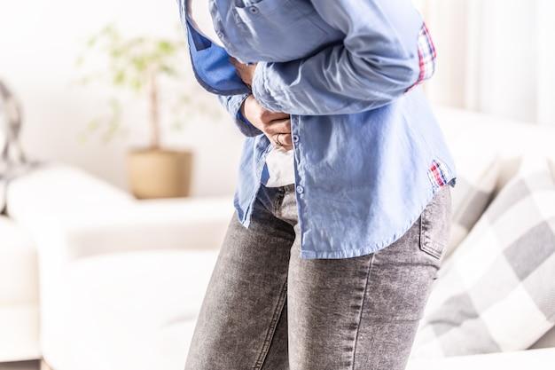 Detalle de una mujer con dolor de abdominales, vesícula biliar, ovarios, apéndice, hígado o intestinos sosteniendo el vientre con las manos.