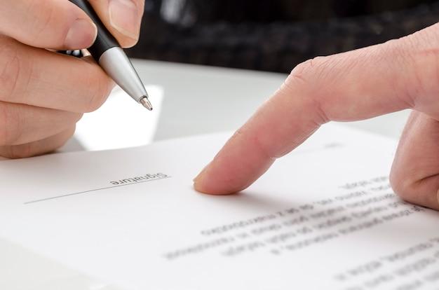 Detalle de una mujer firmando un papel. dedo masculino mostrando dónde firmar.