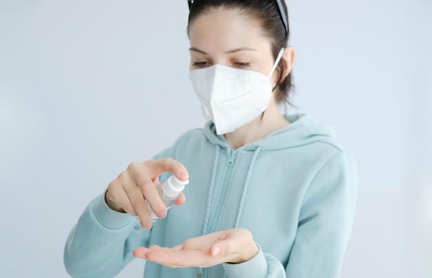 Detalle de mujer joven limpiándose las manos, usando desinfección en gel líquido. protección del hogar covid-19.