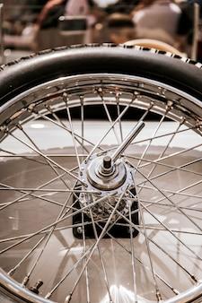 Detalle de un neumático con llanta de rayo en coche de época.