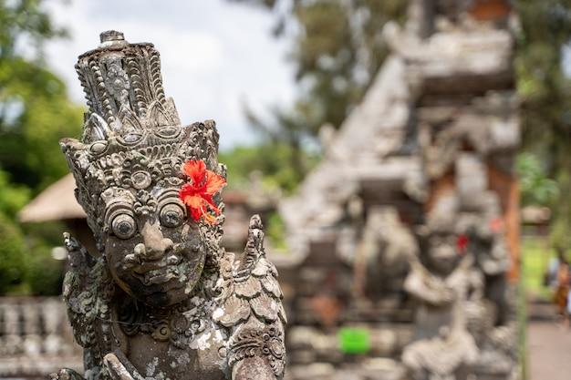 Detalle de la parte superior de una estatua de piedra en un templo hindú con una flor roja