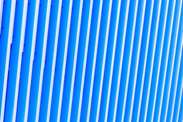 Detalle del patrón de fachada de metal rayado para fondo azul.