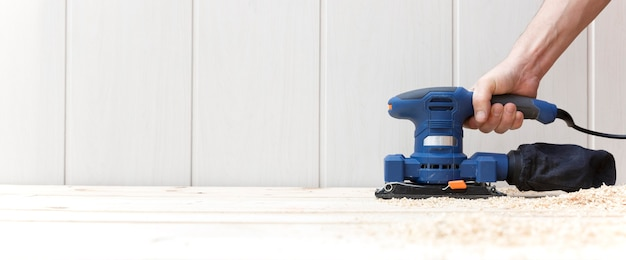 Detalle de la persona que trabaja con una lijadora eléctrica en el piso de madera natural de su casa.