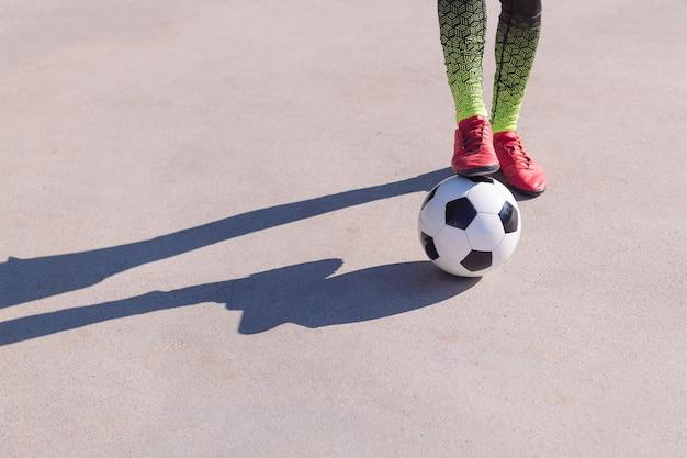 Detalle de un pie en la pelota sobre un piso de concreto