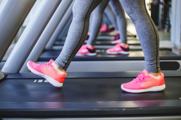 Detalle de las piernas de las mujeres corriendo en cintas de correr.