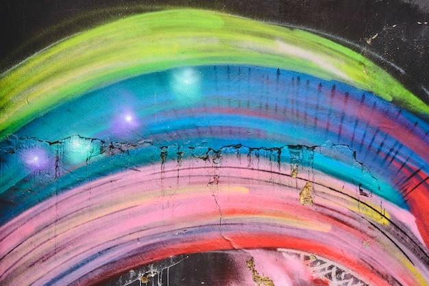 Detalle de una pintada anónima de la calle con muchos colores, fondo urbano alegre.