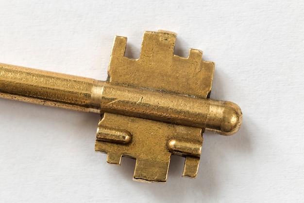 Detalle del primer de la vieja llave de acero bien usada aislada en el espacio blanco de la copia. concepto de seguridad y protección.