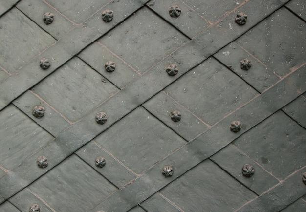 Detalle de puerta de hierro forjado con placa de metal retorcida y clavos esculpidos