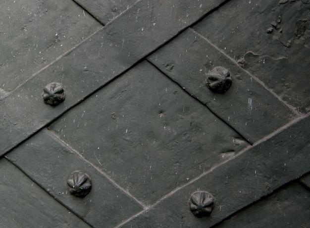 Detalle de puerta de hierro forjado con una placa metálica retorcida y clavos esculpidos. de cerca