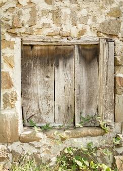 Detalle de la puerta de madera antigua vintage en un muro de piedra
