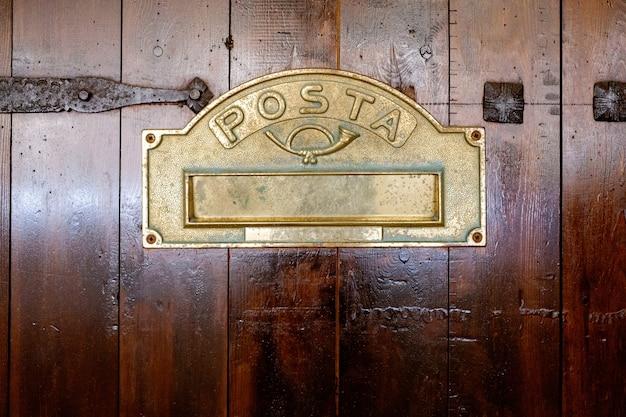 Detalle de una puerta de madera con un buzón con el texto posta, letras en español, en un estilo retro típico de las zonas rurales.