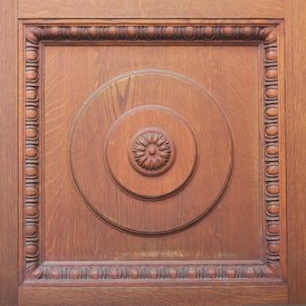 Detalle de la puerta de madera marrón tallada con adorno