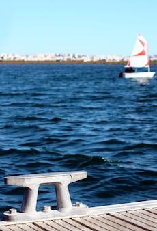 Detalle de un punto de anclaje moderno, en el fondo desenfocado hay un pequeño bote de vela y la ciudad.