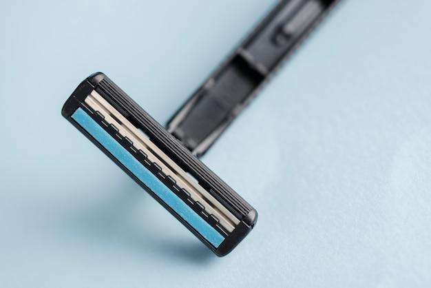 Detalle de rasuradora negra desechable contra fondo azul.