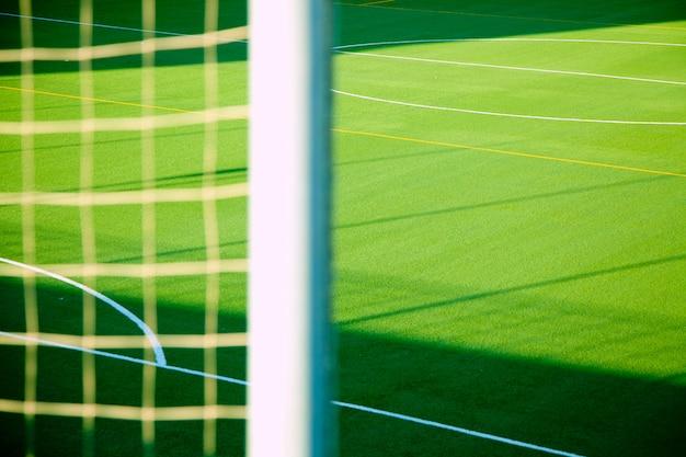 Detalle de red de futbol verde con cancha deportiva.
