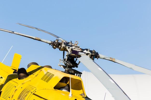 Detalle del rotor de un helicóptero amarillo con el cielo al fondo.