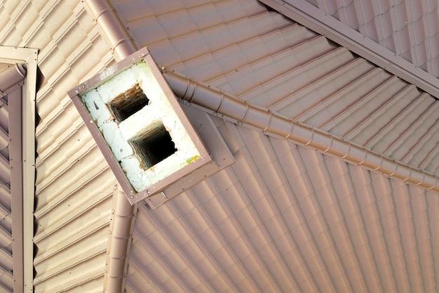Detalle de la superficie del techo de una casa cubierta con láminas de tejas de metal marrón.