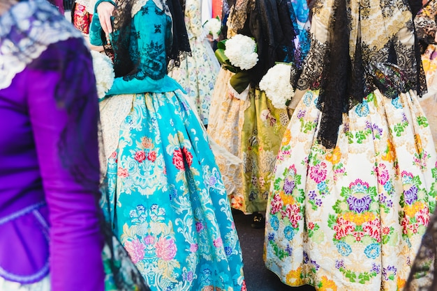 Detalle del tradicional vestido de fallera valenciano español, telas coloridas con intrincados bordados.