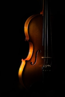 Detalle de violín sobre un fondo negro entre luces o sombras