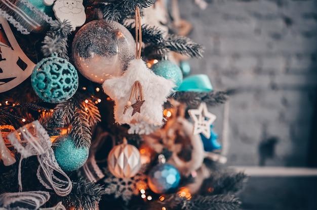 Detalles de un árbol de navidad decorado en turquesa oscuro y naranja.