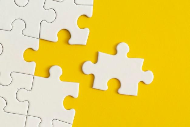 Detalles blancos del rompecabezas sobre fondo amarillo trabajo en equipo de estrategia empresarial