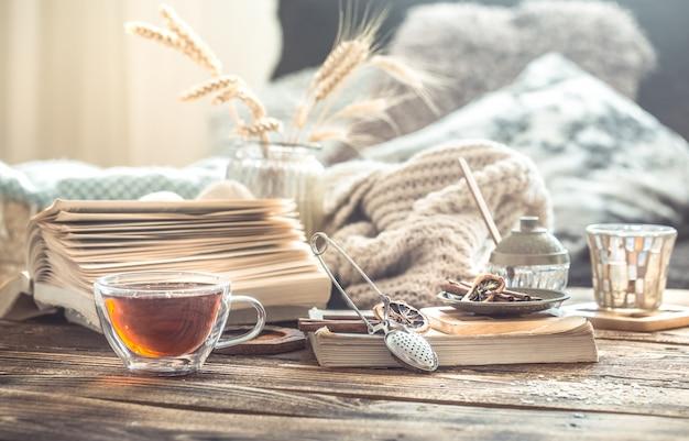 Detalles de bodegones del interior de una casa en una mesa de madera con una taza de té