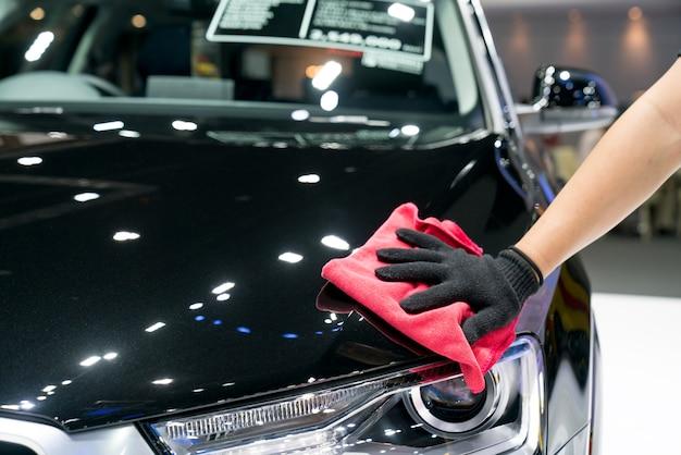 Detalles del coche: el hombre sostiene la microfibra en la mano y pule el automóvil.