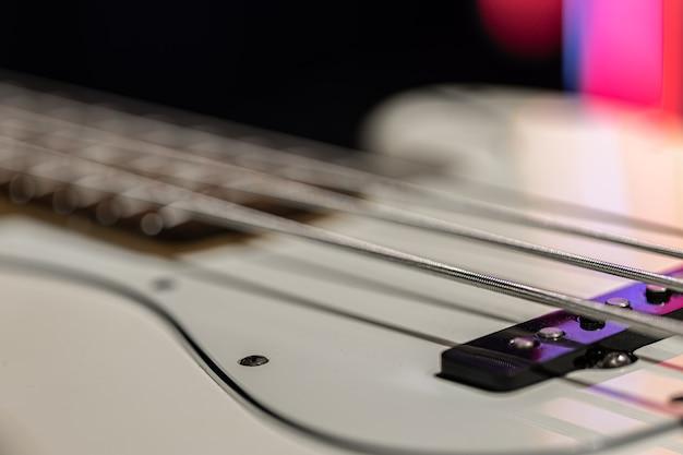 Detalles de cuerdas de bajo de guitarra, cerca de las cuerdas de hierro sobre fondo borroso.