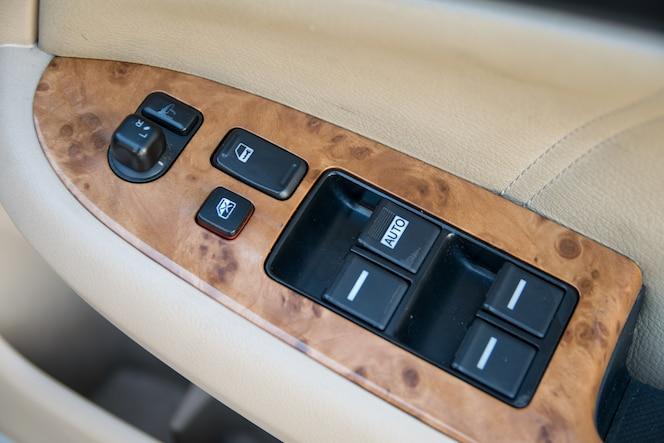 Detalles del interior del coche de la manija de la puerta con controles y ajustes de ventanas