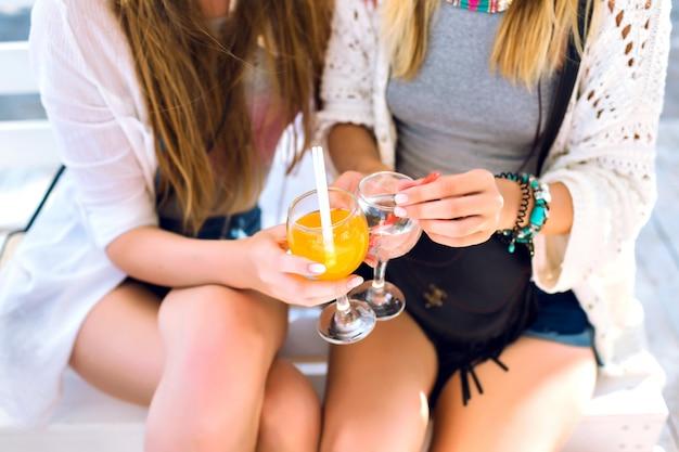 Detalles de la fiesta de cerca, dos amigos que se divierten en la fiesta del bar de la playa, se centran en cócteles, ambiente feliz de vacaciones, diversión loca, ropa brillante y elegante.