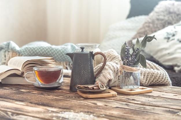 Detalles de la naturaleza muerta del interior de una casa en una mesa de madera con una taza de té