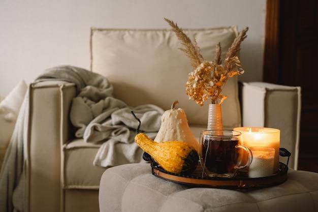 Detalles de naturaleza muerta en el interior de la casa de la sala de estar. calabaza y taza de té con velas en una bandeja para servir. descanso y lectura. otoño acogedor