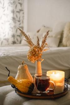 Detalles de naturaleza muerta en el interior de la casa de la sala de estar. calabaza y taza de té con velas en una bandeja para servir. otoño acogedor