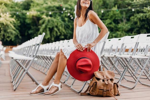 Detalles de primer plano de mujer con vestido blanco, sombrero rojo sentado en el teatro al aire libre de verano solo en una silla, tendencia de moda de estilo callejero de primavera, accesorios, viajar con mochila, piernas delgadas en sandalias