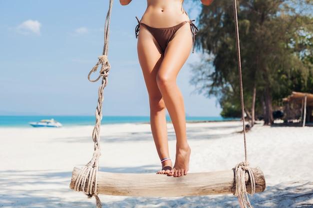 Detalles de primer plano de piernas largas y delgadas bronceadas de joven atractiva mujer sexy de vacaciones en tailandia, columpio en el mar, playa tropical, cuerpo delgado perfecto, viajando en asia, feliz, soleado, estilo de verano