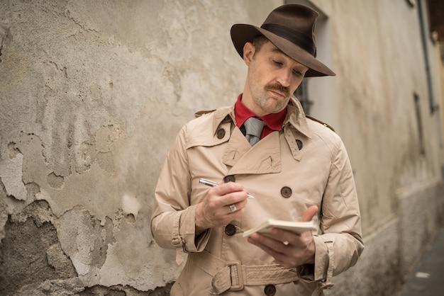 Detective escribiendo en un cuaderno mientras está cerca de una pared vieja