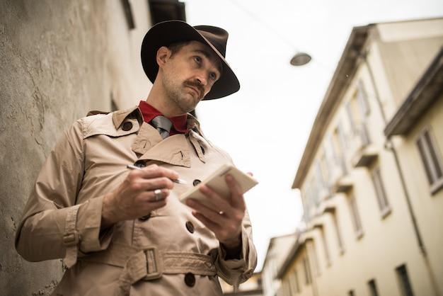 Detective escribiendo en un cuaderno mientras está parado contra una pared vieja