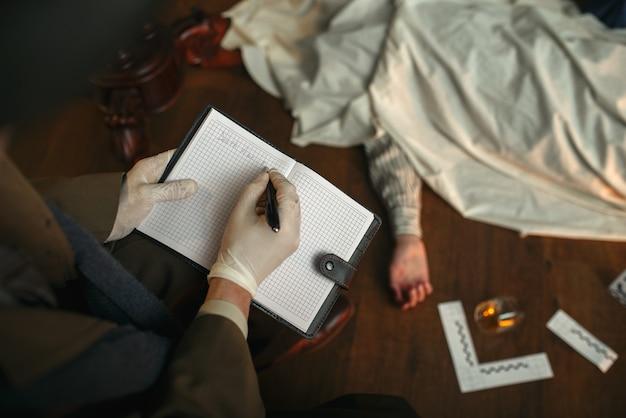Detective masculino con cigarro escribe en cuaderno