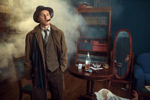 Detective masculino con cigarro tiene carpeta de cuero, víctima debajo de la capa en la escena del crimen