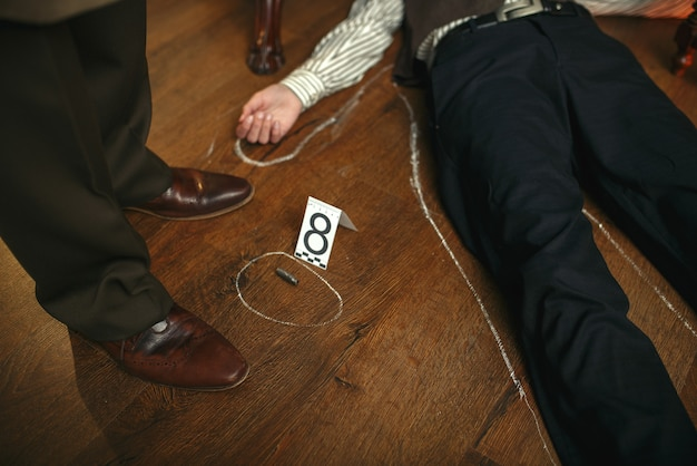 Detective masculino y el cuerpo de la víctima en círculos con tiza en la escena del crimen