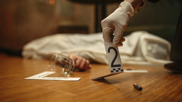 Detective masculino en guantes mirando pruebas en la escena del crimen