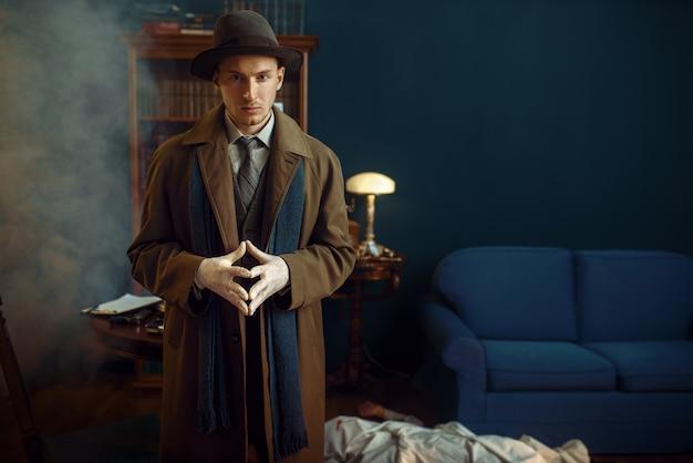 Detective masculino en guantes, víctima debajo de la capa