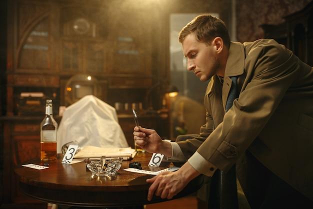 Detective masculino con pinzas pone la evidencia en una bolsa en la escena del crimen